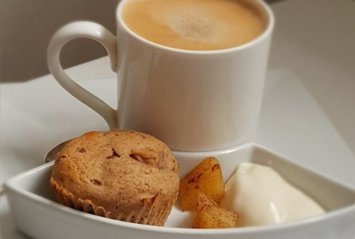 muffin on a plate with frothy coffee