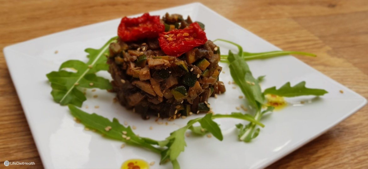 side view ofcooked diced mushrooms and aubergine on a plate