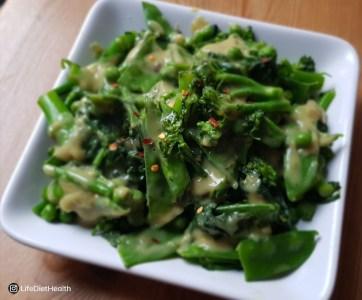 green veg in sauce on white plate