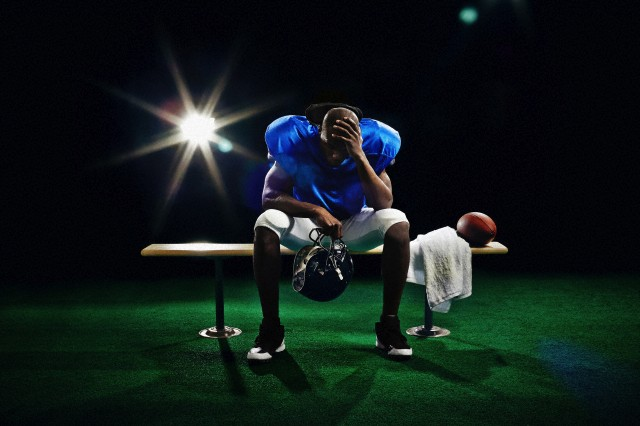 Portrait of american football player with head in hand --- Image by © Edwin Jimenez/Corbis