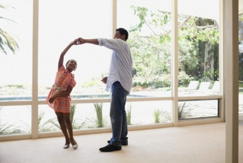 Father and daughter dancing together --- Image by © Blue Images