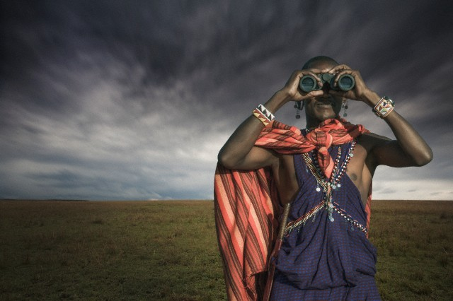 Masai warrior looking through binoculars, Masai Mara National Park, Kenya