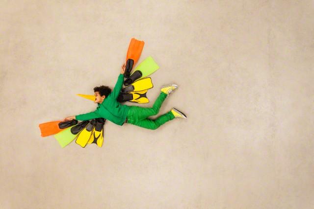 Boy dressed up as flying bird --- Image by © Leander Baerenz