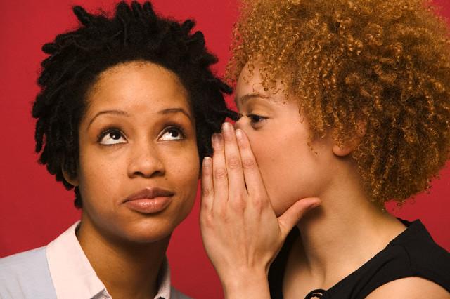Woman Whispering into Friend's Ear --- Image by © John Henley
