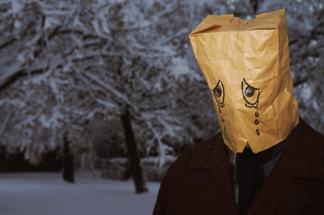 Man wearing paper bag with crying eyes drawn, standing in winter scenery