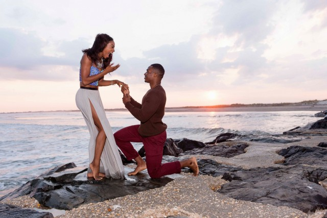 10 Sep 2015, Stone Harbor, New Jersey, USA --- Mid adult man kneeling on rocks beside sea, proposing to young woman --- Image by © Zave Smith/Corbis