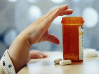 child reaching for medication bottle