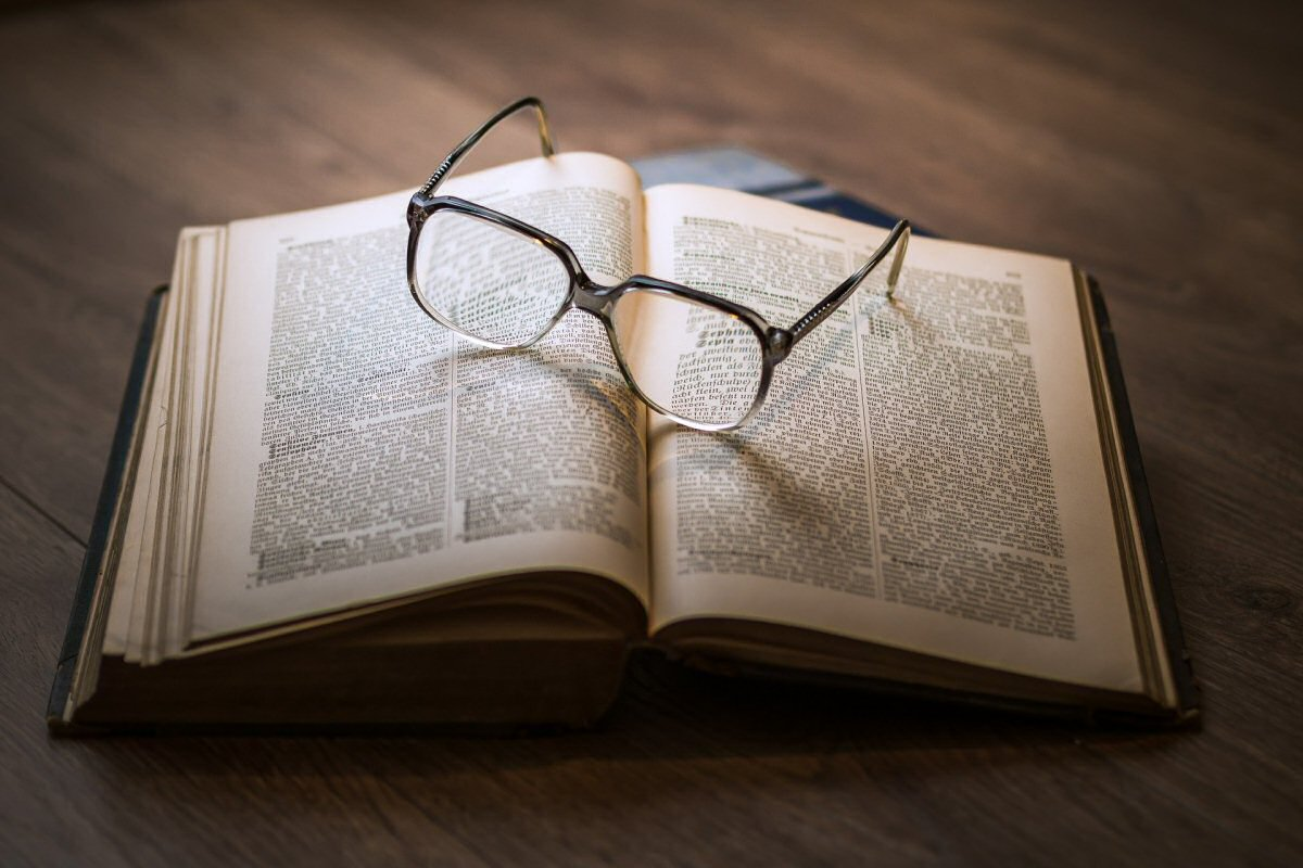 book on table with reading glasses