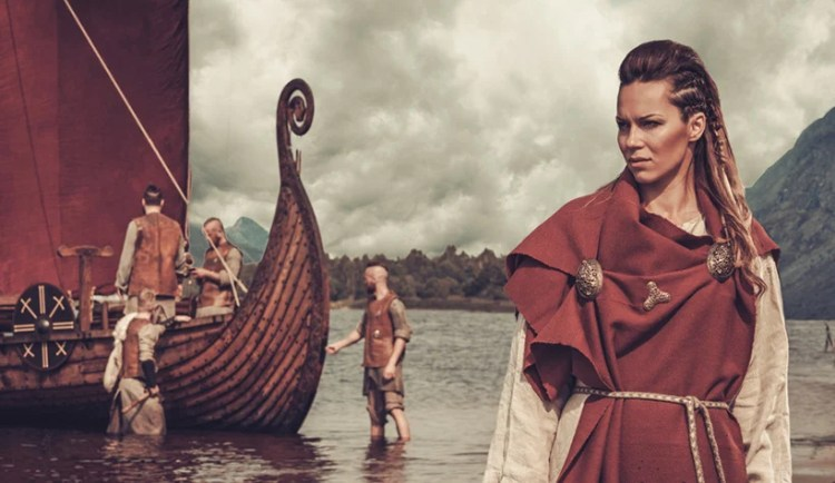 Viking woman standing by ship in the water