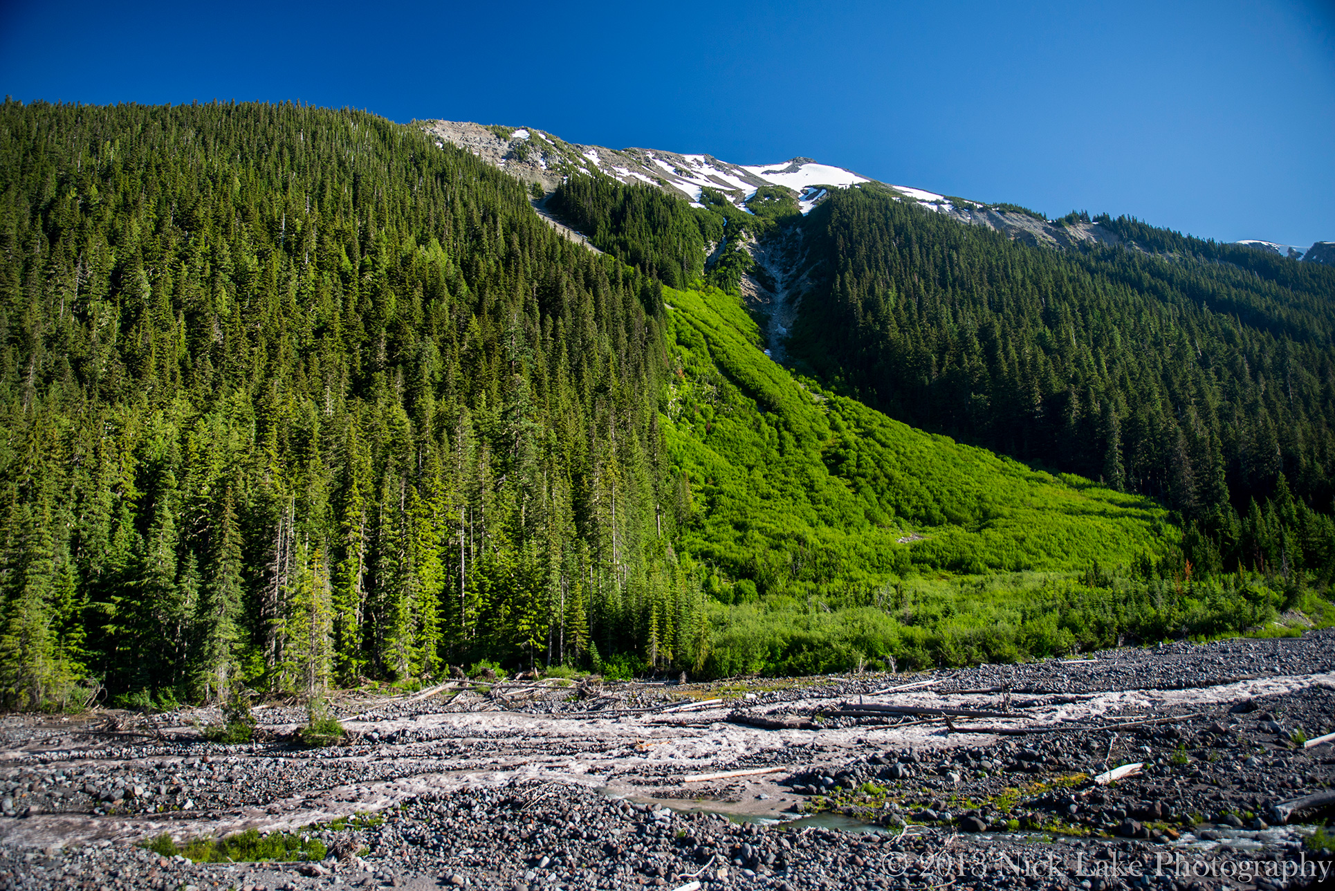A long, slender ridge approaches the summit of Mt. Rainier above White River