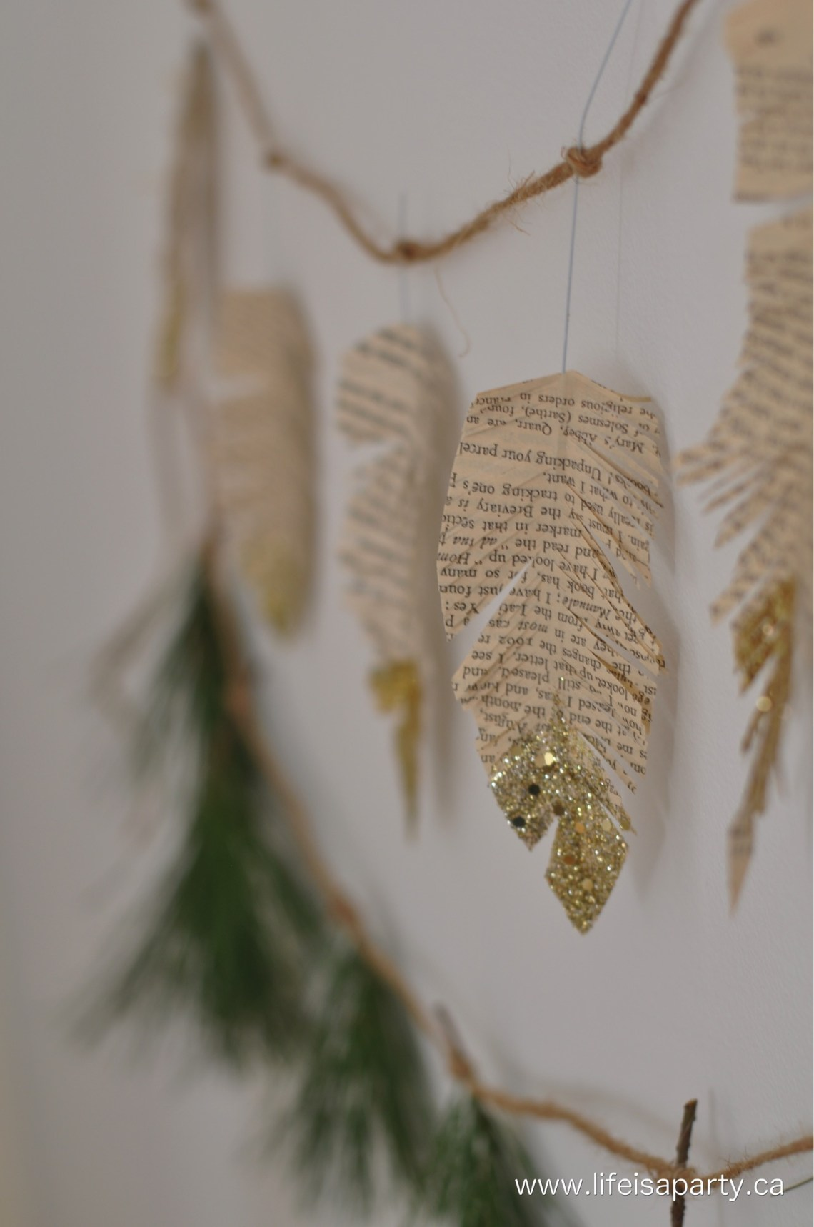 How To Make Book Page Paper Feathers: using old book pages, a glue stick and a wire for a center make beautiful feathers to use as a garland, gift topper, or Christmas tree ornament. Make it festive by adding gold glitter. Easy Holiday DIY.