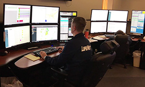 LifeNet dispatcher sits at a computer in the comm center dispatching a call.
