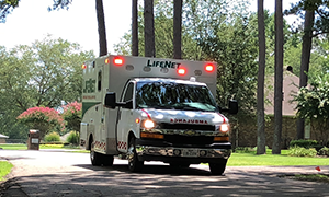 LifeNet Ground Ambulance travels down the road with lights flashing.