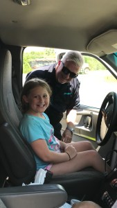 A girl smiles sitting behind the wheel of a LifeNet Ambulance in Hot Springs with paramedic Terry Childers.