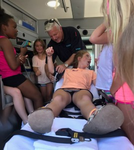A kid at Tumble Jungle reacts to being put on a cot during an ambulance demonstration in Hot Springs.
