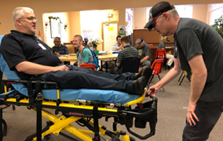 Kevin Plunk, Paramedic for LifeNet EMS, lets a resident push a cot button.