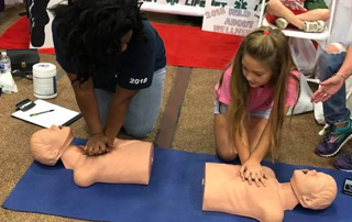 LifeNet staff demonstrate compression only CPR with a young girl at Wild About Wellness Health Fair in Texarkana.