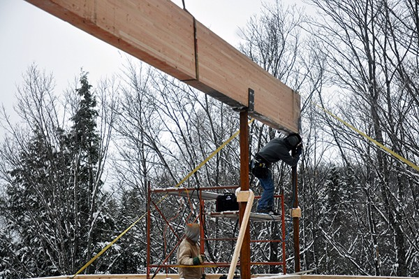 Cabin tack welding the glulam in place