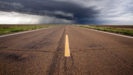A severe thunderstorm passes over the highway in western Kansas