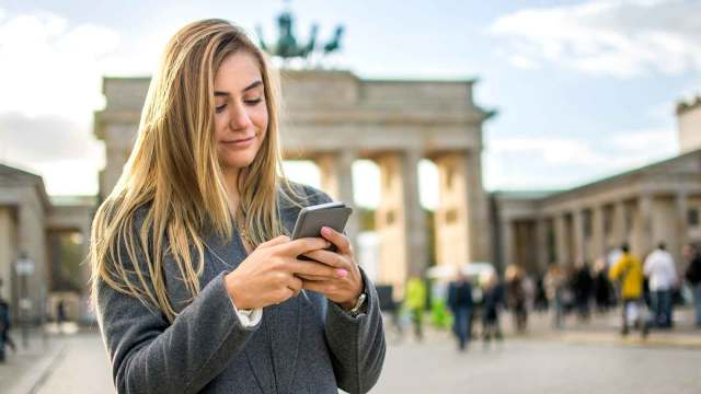 Woman checking her phone in front of the Brandenburg Gate in Berlin, Germany.