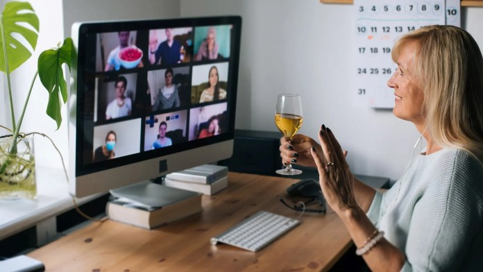 A woman holding a glass of wine while chatting with a friends on a Zoom Call.