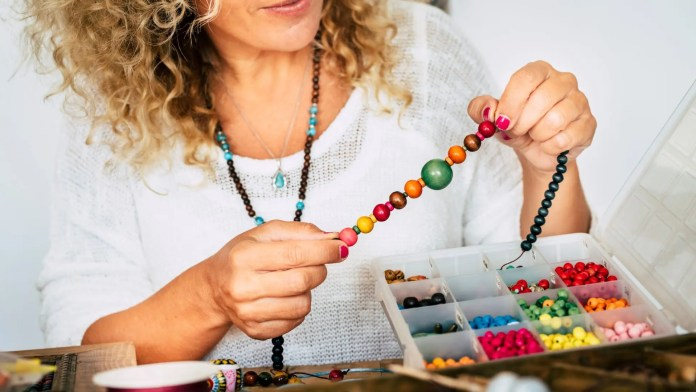 A woman making a beaded necklace.
