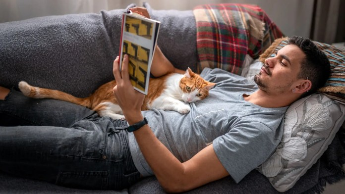 A man lying on a couch reading with a cat on his chest.