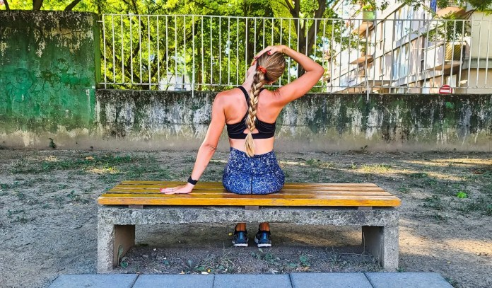 Woman doing a side neck stretch on a bench in the park.