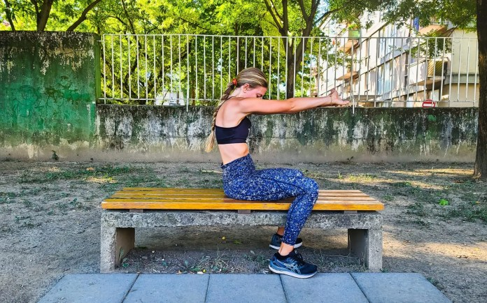 Woman performing a shoulder stretch on a bench in the park.