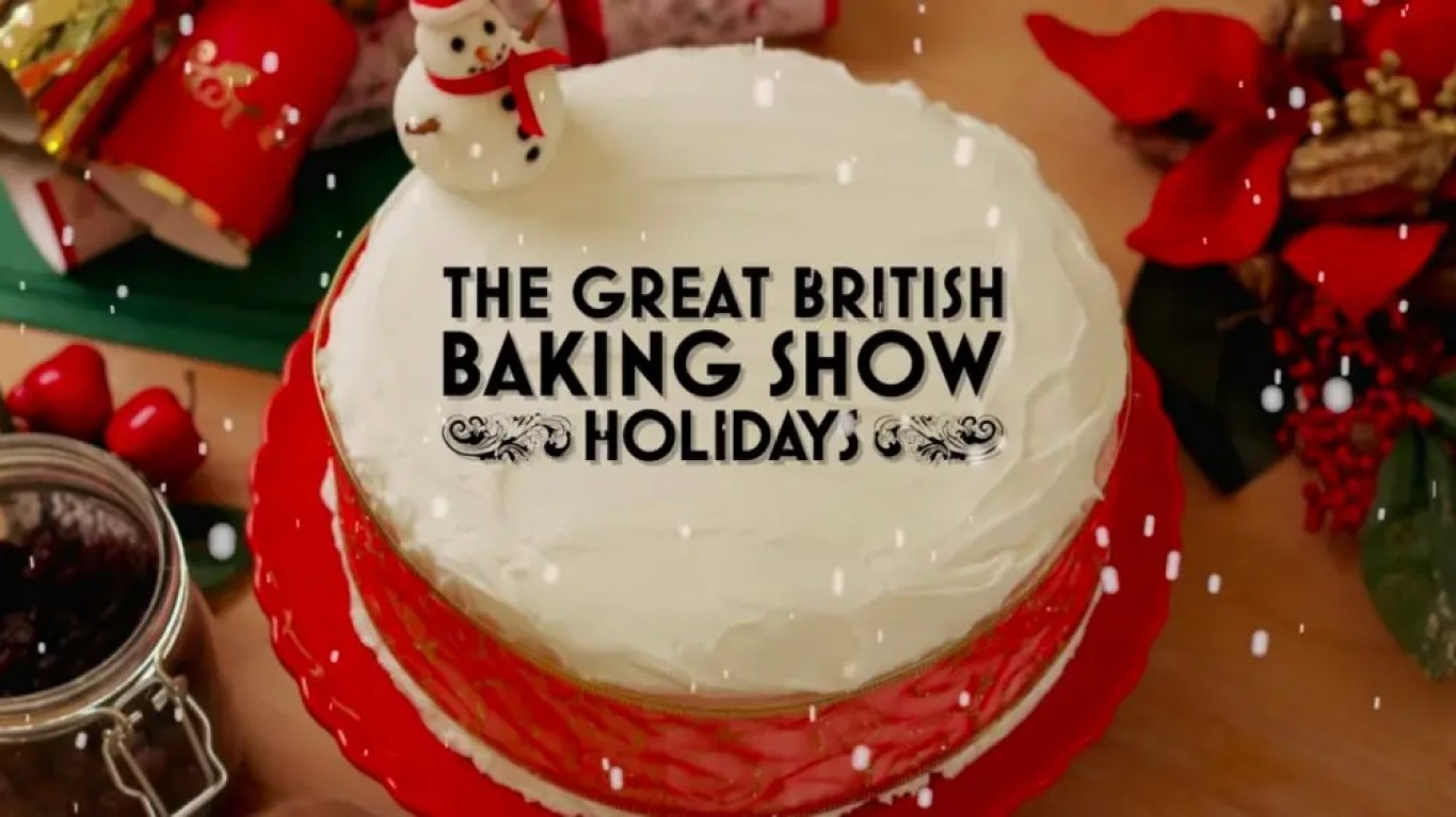 A cake with snow following around it has The Great British Baking Show logo on top.