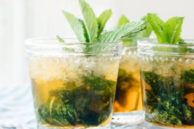 Three cups filled with maple mint bark and decorated with fresh mint leaves.