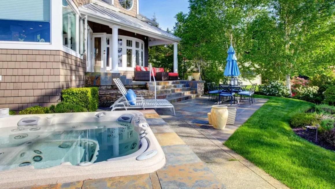 Красивый дом с садовой мебелью, красивым ландшафтным дизайном и джакузи.