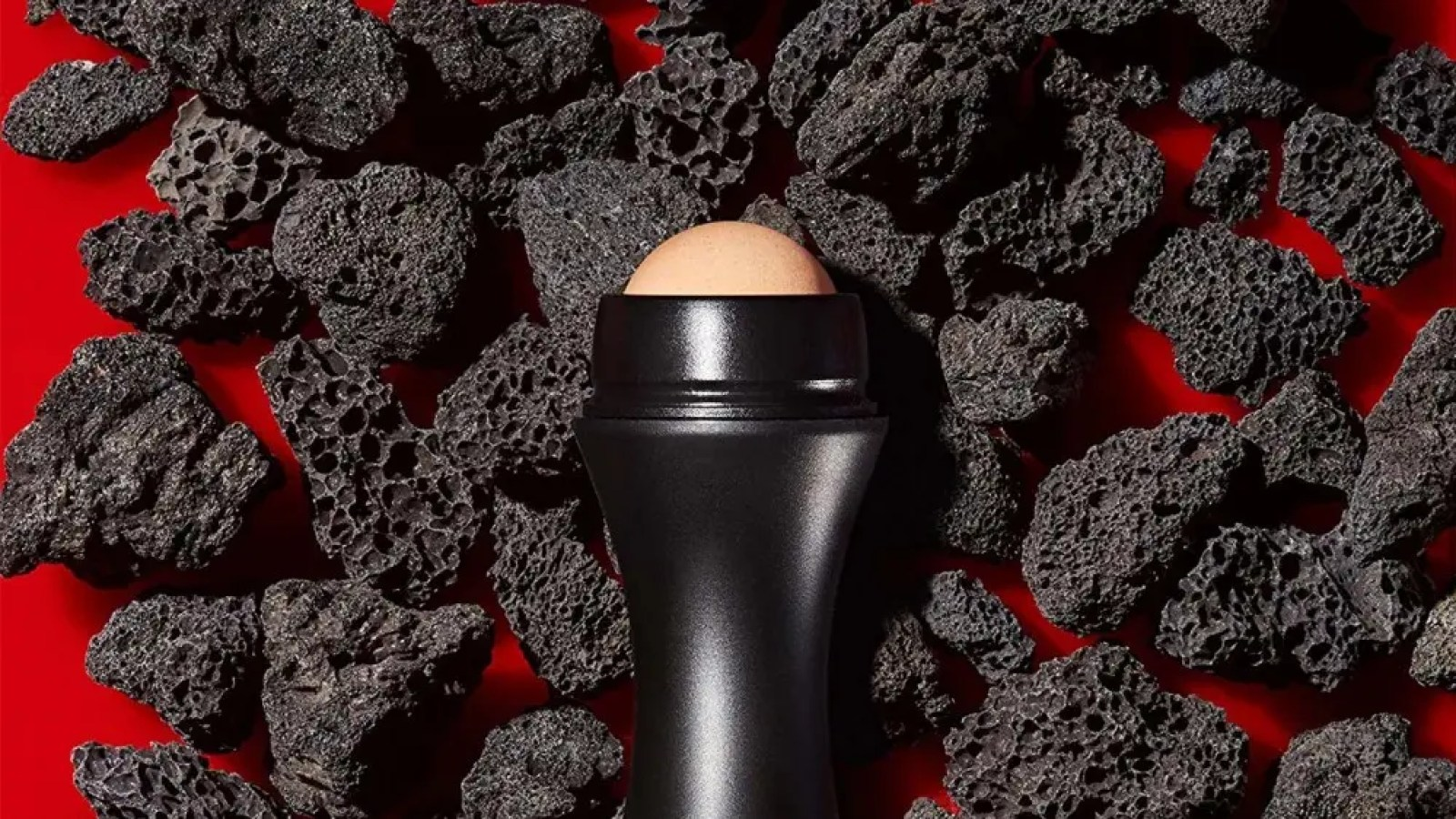 A Revlon volcanic roller, resting on a pile of volcanic pumice stone.