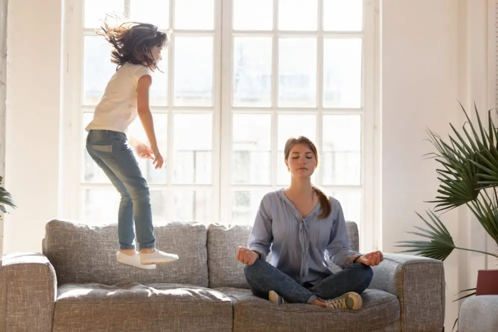 A woman meditating while a little girl jumps on the sofa next to her.