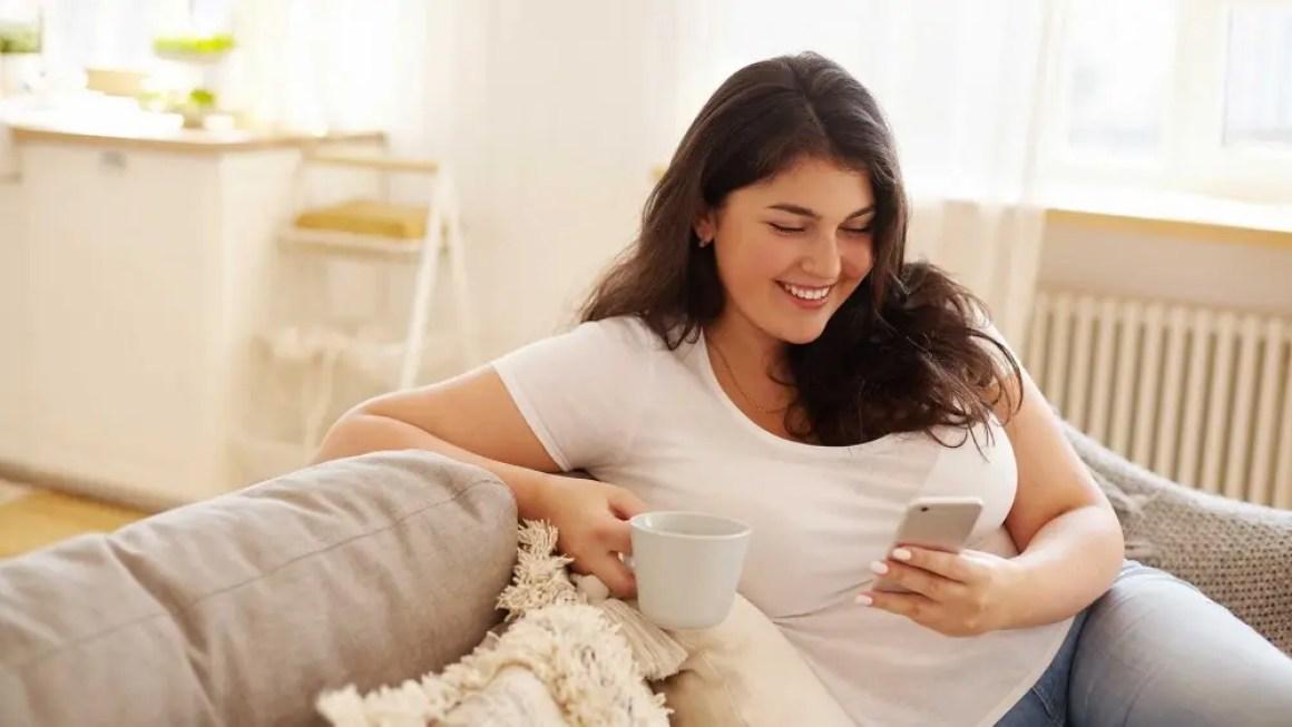 Молодая женщина сидит на диване, пьет кофе и улыбается, используя приложение счастья на своем смартфоне.