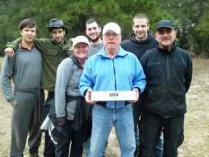 Walt, an instructor is holding a SOG Knife box with a group of Texas Students and staff.