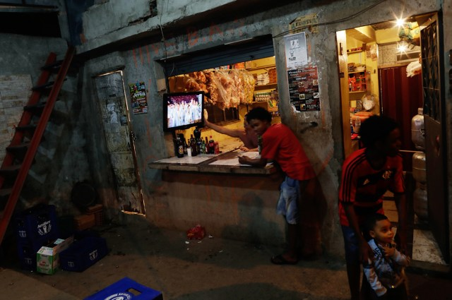 Locals in Rio watch the opening ceremony on TV