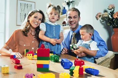 kids with toy blocks playing with mom and dad