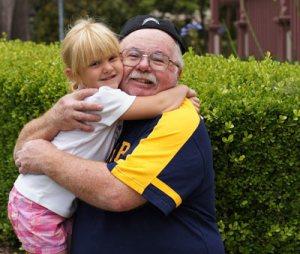 grandfather hugging grand daughter