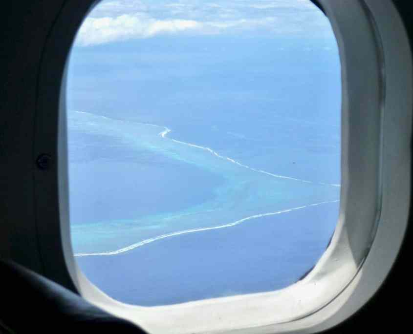 View out of the window of the little twin otter showing an island with coral atoll