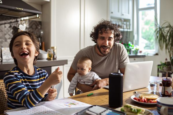 Family using a smart speaker while doing schoolwork at the table.