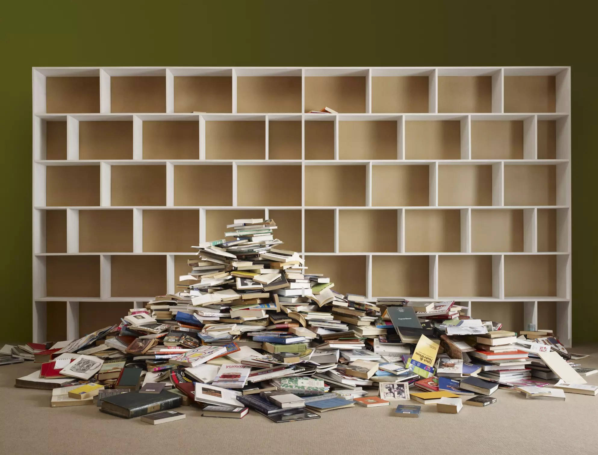 Photo of books on a floor in front of empty bookshelves - The Internet Tips