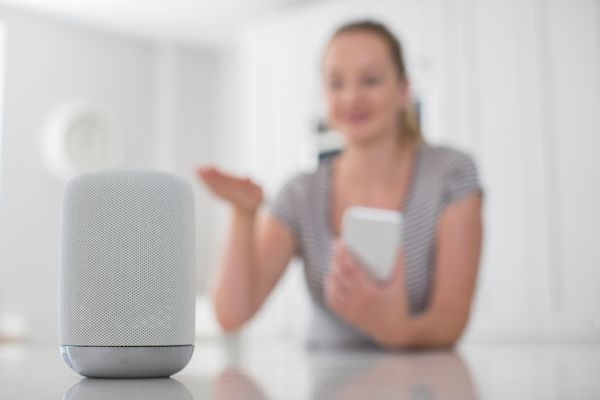 A woman using her mobile device and talking to a smart speaker.