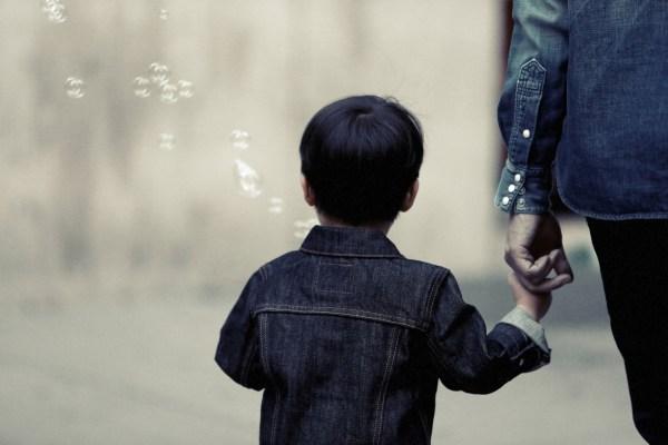 Mom holding boy's hand