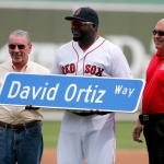Lee County commissioners John Manning, left, and Cecil Pendegrass, right, present Boston Red Sox's David Ortiz with a street sign after city leaders honored Ortiz by renaming a street by the ballpark in his name during a ceremony before a spring training baseball game against the Baltimore Orioles, Monday, March 28, 2016, in Fort Myers , Fla. Ortiz played his last spring training home game at jetBlue Park Monday. (AP Photo/Tony Gutierrez)