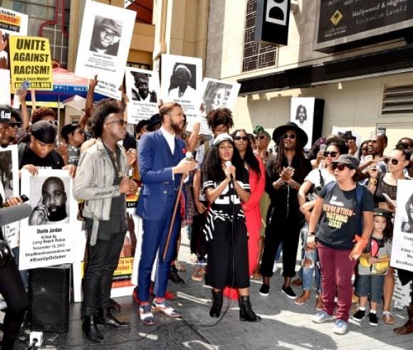 ז'אנל מונה עם הזמר Jidenna (בחליפה כחולה) במחאה נגד אלימות משטרתית. הוליווד, 21 באוגוסט