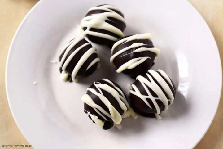 Above view of the five Oreo Truffles on a plate covered in melted chocolate and drizzled with melted white chocolate for the professional and indulgent finish.