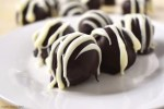 Close up of the Oreo Truffles on a plate with other truffles in the background. Covered in melted chocolate and drizzled with melted white chocolate for the professional and indulgent finish.