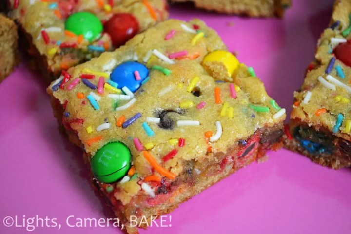 Rainbow M&M Blondies: Soft, gooey and chewy blondies filled with chocolate chips, M&MS and rainbow sprinkles for good measure! These are cute, fun and clolourful. Click the photo for the #recipe #rainbowblondies #m&mblondies #cakebatterblondies