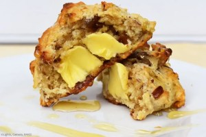 Easy Date Scones chopped in half with melted butter and runny honey drizzled over the plate.